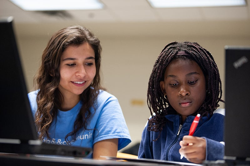 Milena Gonzalez works with a local middle school student at a coding&&community workshop.