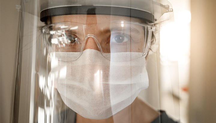 Person wearing face shield, face mask, and protective glasses