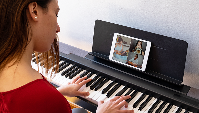 Person plays the piano while teleconferencing with other musicians