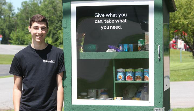 Adam Fellows stands in front of the food pantry he built