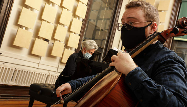 Two musicians play their instruments while wearing face masks.