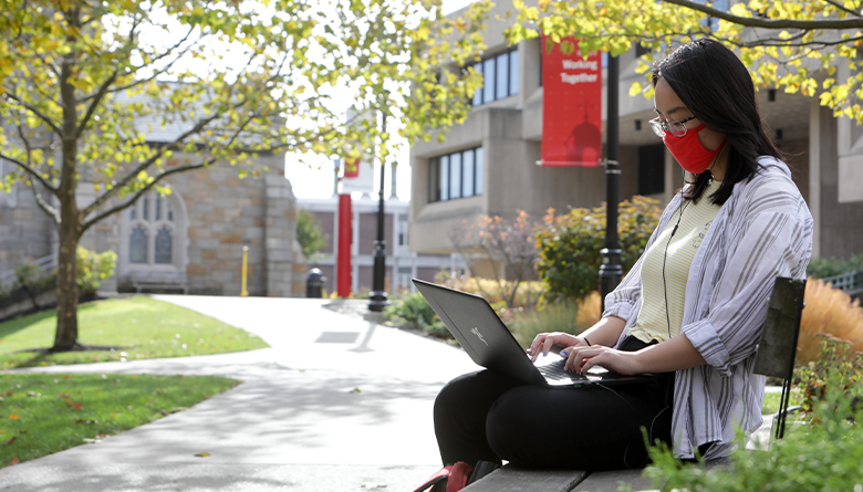 Student wearing a face mask working on her laptop while sitting on a bench.