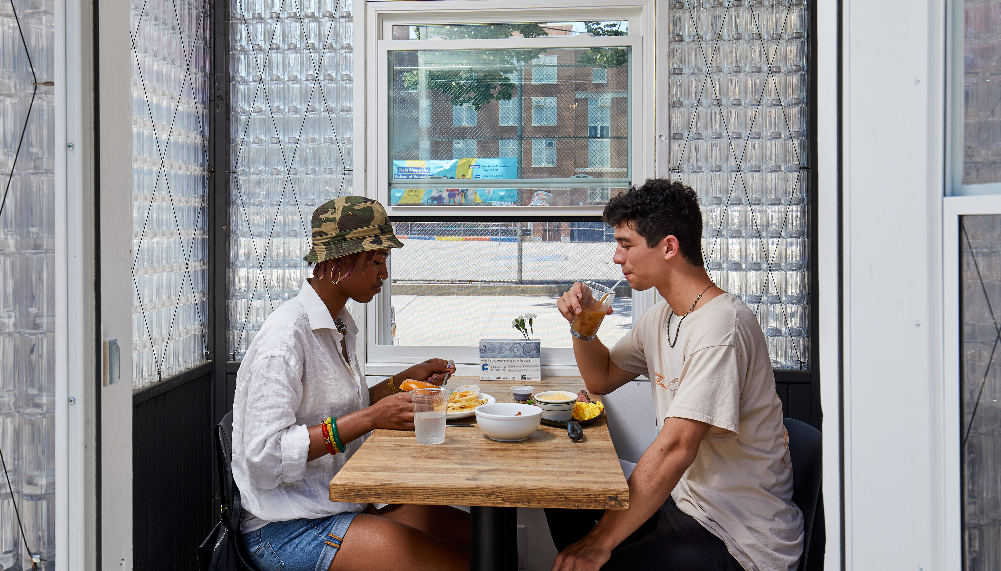 Two people eating inside a Friendship Cabin