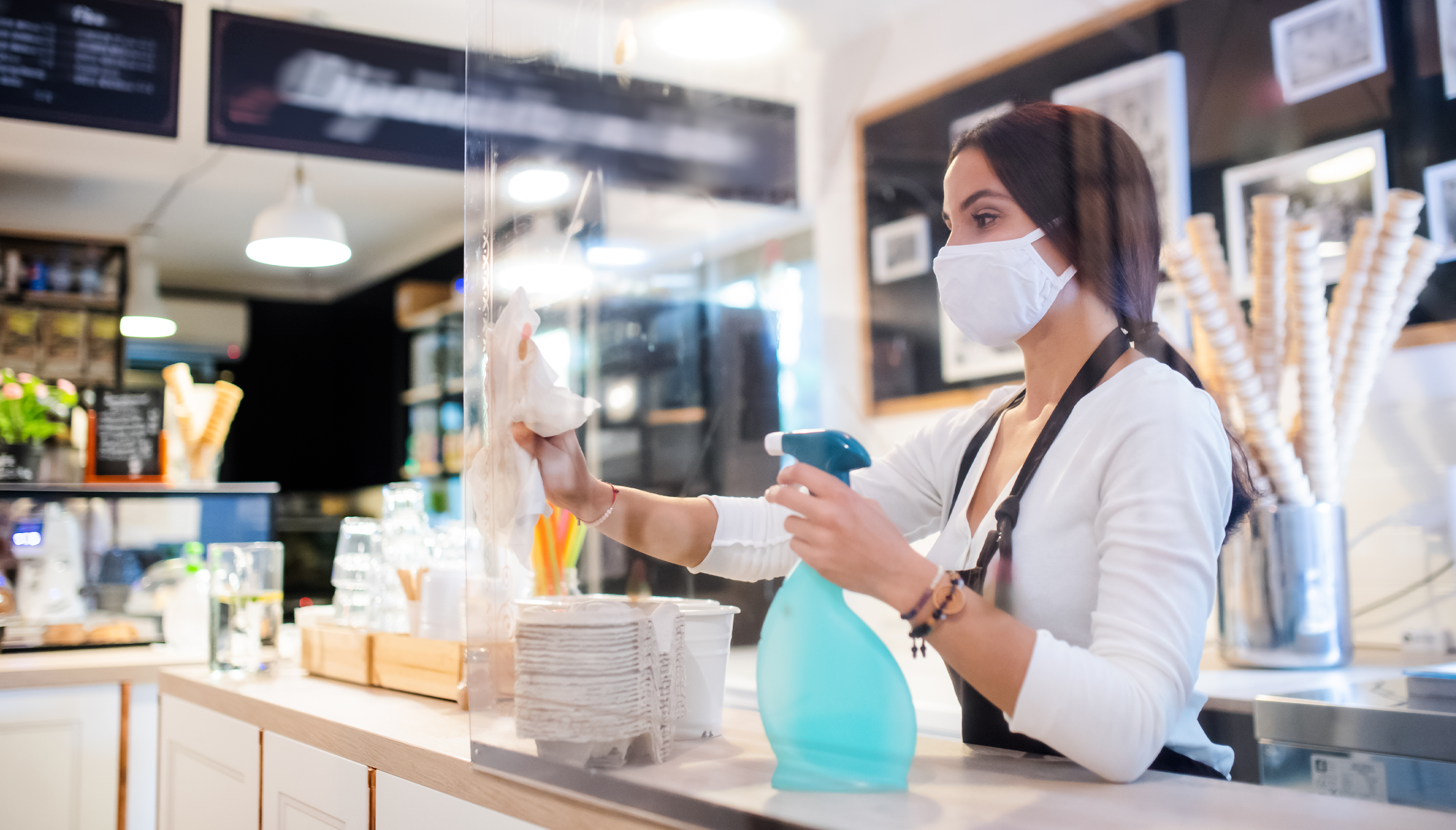 Woman wearing face mask working in cafe.